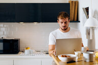 Young man using laptop in kitchen - CUF48111
