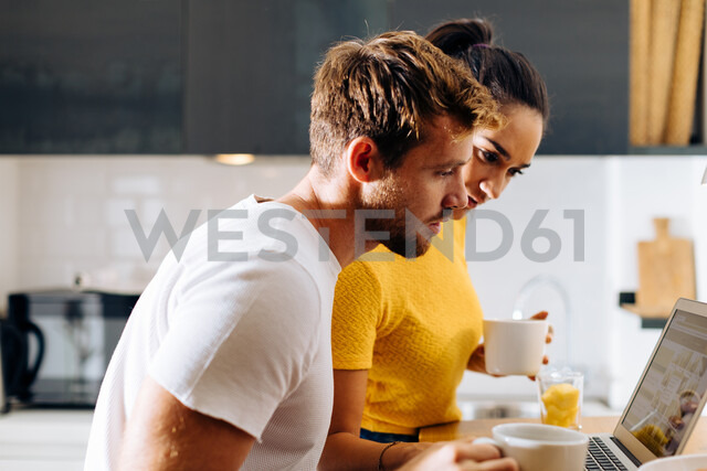 Young couple using laptop in kitchen - CUF48114