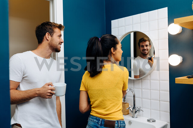 Young couple talking in front of wall mirror in bathroom - CUF48123