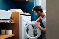 Young man putting laundry into washing machine at home - CUF48126