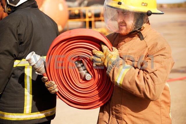 Fireman carrying fire hose reel, Darlington, UK - CUF48138