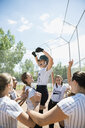 Enthusiastic middle school girl softball team celebrating on baseball diamond - HEROF05245
