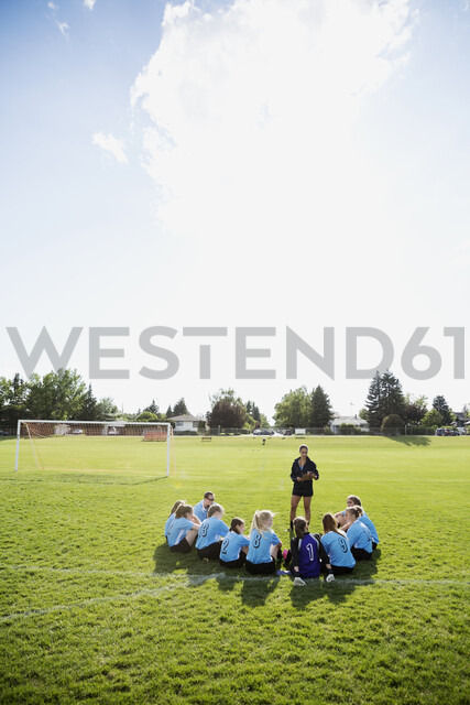 Coach talking to middle school girl soccer team on sunny field - HEROF05248