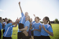 Exuberant middle school girl soccer team celebrating and cheering on field - HEROF05251