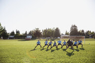 Coach and middle school girl soccer team stretching at practice on sunny field - HEROF05260