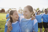 Enthusiastic middle school girl soccer players hugging on sunny field - HEROF05263