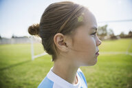Close up profile pensive middle school girl soccer player looking away - HEROF05269