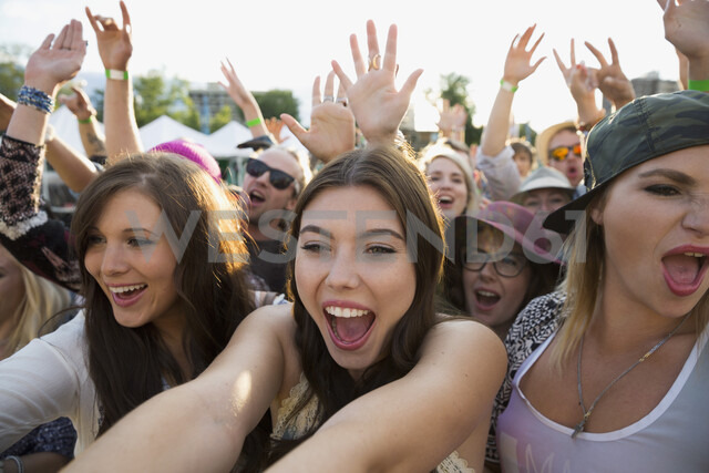 Enthusiastic young women cheering in crowd at summer music festival - HEROF05278