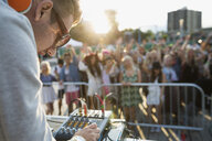 DJ adjusting equipment on stage at summer music festival - HEROF05281