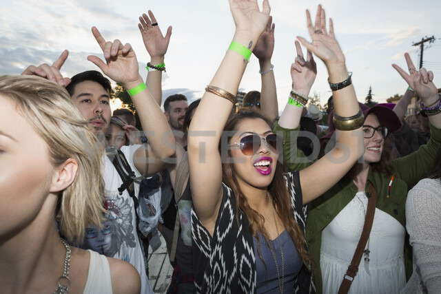 Enthusiastic young woman cheering in crowd at summer music festival - HEROF05284