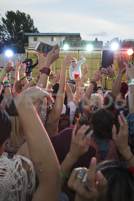 Crowd cheering musician on illuminated stage at summer music festival - HEROF05287 - Hero Images/Westend61