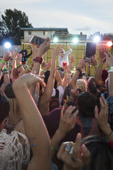 Crowd cheering musician on illuminated stage at summer music festival - HEROF05287