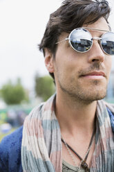 Close up young brunette man wearing sunglasses looking away - HEROF05290