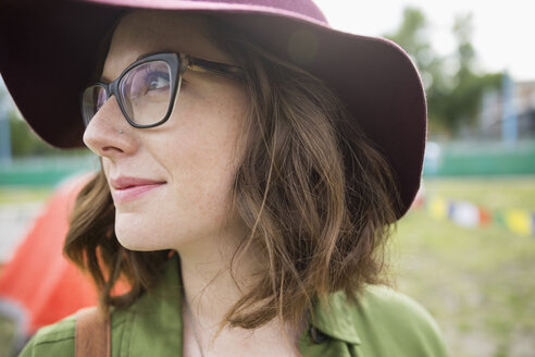 Close up portrait pensive young brunette woman wearing floppy hat and eyeglasses looking away - HEROF05302