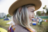 Close up portrait young woman with chalk dyed hair wearing hat looking away at summer music festival campsite - HEROF05314
