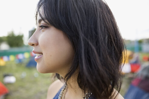 Close up profile portrait smiling young woman with black hair looking away at summer music festival campsite - HEROF05317