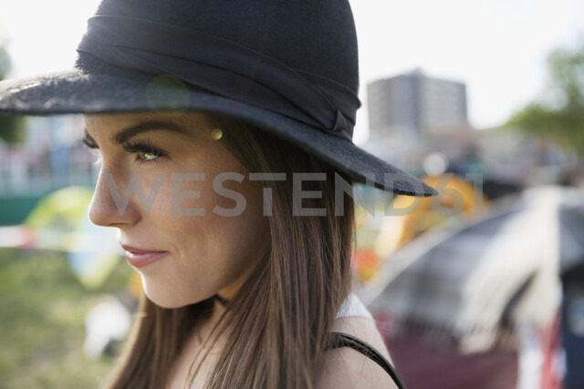 Close up portrait pensive young brunette woman wearing hat looking away at summer music festival campsite - HEROF05320
