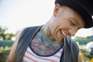 Close up portrait laughing young man with tattooed chest looking down - HEROF05323