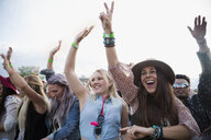Enthusiastic young women cheering in crowd at summer music festival - HEROF05332