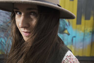 Close up portrait serious young brunette woman wearing hat - HEROF05335