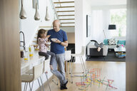Father and daughter eating breakfast cereal in morning kitchen - HEROF05353