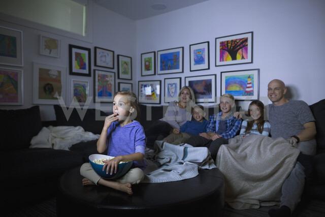 Family eating popcorn watching movie in dark living room - HEROF05356
