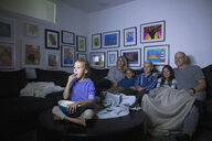 Family eating popcorn watching movie in dark living room - HEROF05356