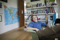 Enthusiastic boy listening to music with headphones in bedroom - HEROF05362