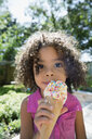 Close up portrait girl eating ice cream cone with sprinkles in sunny backyard - HEROF05368