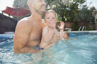 Father holding son in sunny swimming pool - HEROF05371