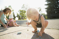 Family drawing with sidewalk chalk on sunny sidewalk - HEROF05374