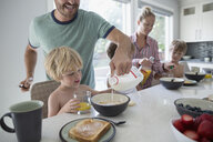 Father pouring milk into cereal for son at breakfast - HEROF05383