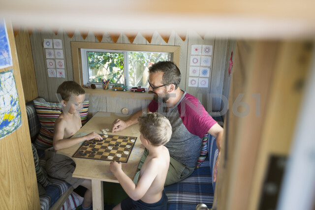 Father and sons playing checkers at table in treehouse - HEROF05386