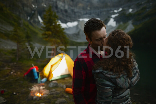 Couple kissing near campfire and tent at remote campsite - HEROF05398