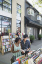 Couple browsing book at bookstore storefront sidewalk bin - HEROF05410