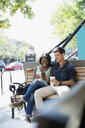 Couple drinking coffee and using cell phone on sunny urban bench - HEROF05413