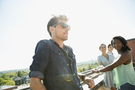 Confident man wearing sunglasses on sunny rooftop - HEROF05419