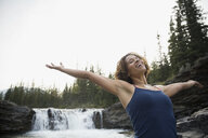 Exuberant woman with arms outstretched near waterfall - HEROF05431