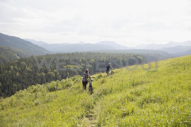 Couple walking mountain bikes in remote rural field - HEROF05434 - Hero Images/Westend61