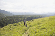 Couple walking mountain bikes in remote rural field - HEROF05434