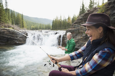 Enthusiastic senior woman fishing catching fish at waterfall - HEROF05437