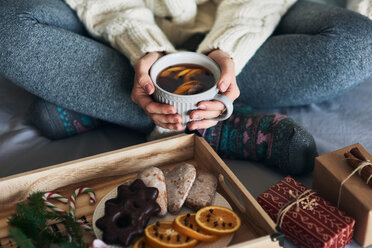 Woman having warm drink in front of tray of Christmas biscuits and gifts - CUF48161