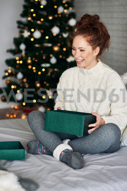 Woman wrapping Christmas presents on bed - CUF48164