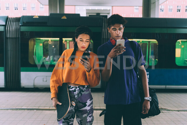 Brother and sister texting at tram stop, Milan, Italy - CUF48173 - Eugenio Marongiu/Westend61