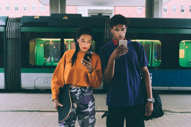 Brother and sister texting at tram stop, Milan, Italy - CUF48173