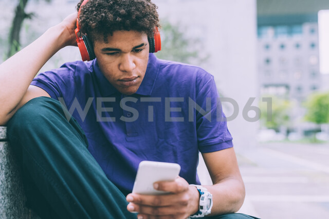 Man texting and using headphones on concrete bench - CUF48194 - Eugenio Marongiu/Westend61