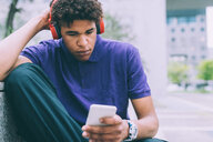 Man texting and using headphones on concrete bench - CUF48194