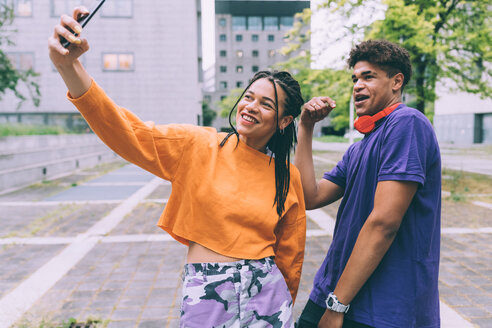 Brother and sister taking selfie - CUF48197