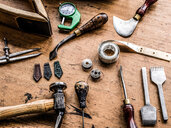Leatherworker's workbench with hammer, tape measure and specialist tools, still life - CUF48209
