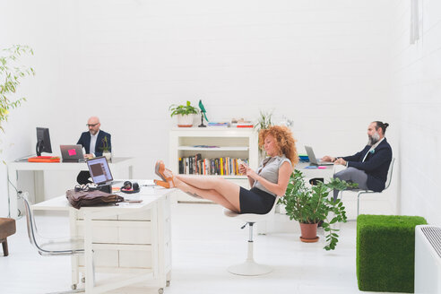 Businessmen working at office desks and businesswoman with her feet up - CUF48227
